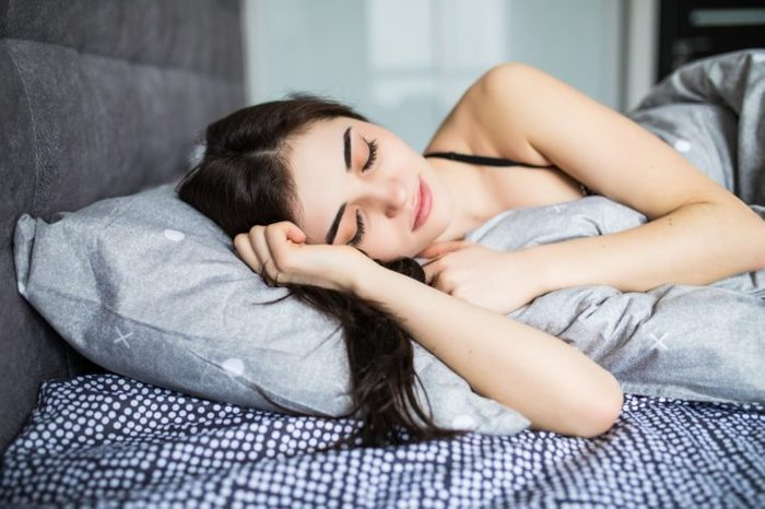 Woman sleeping. Beautiful young smiling woman sleeping in bed