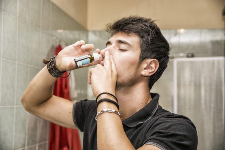 Man applying nasal spray