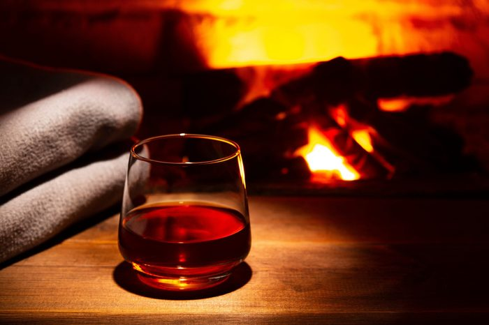 Glass of alcoholic drink wine in front of warm fireplace. Magical relaxed cozy atmosphere near fire.