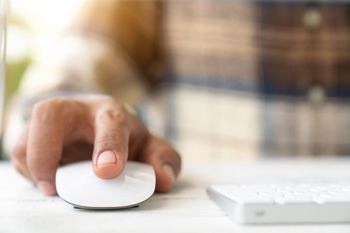 Male hand holding computer mouse with laptop keyboard in the background
