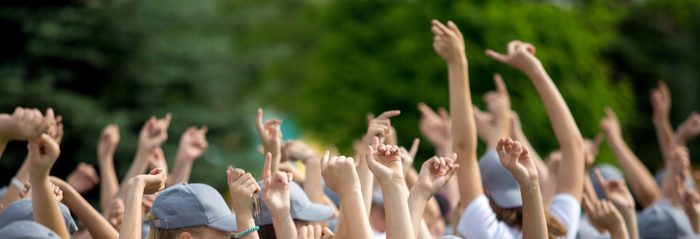 Group of happy young people with hands up to the sky over green natural background