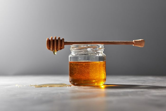 Dripping organic natural fresh honey from glass pot on a gray stone background, place under text. Traditional useful sweetness.