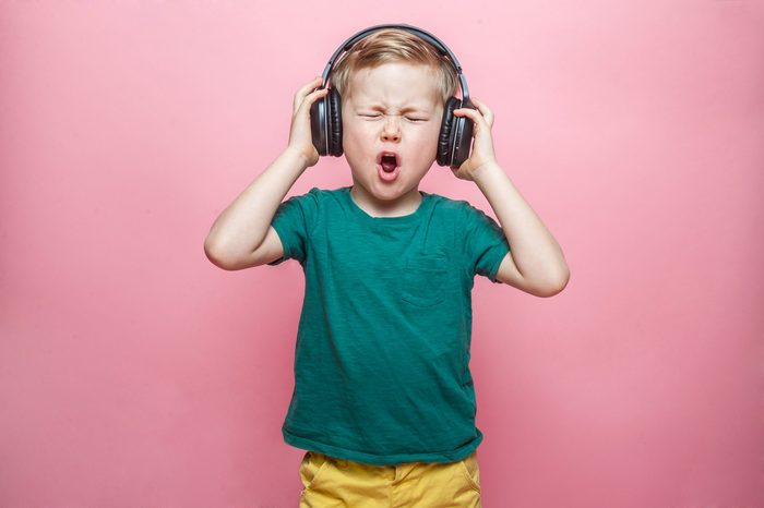 Stylish teen boy listening music in headphones and singing against pink background. School child listening loud music in wireless earphones and dancing.