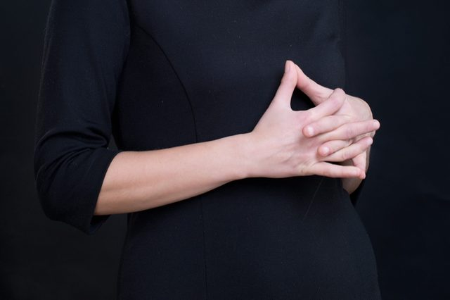 Closeup of interlaced fingers of young woman wearing black dress/ Sign of body language showing uncertainty