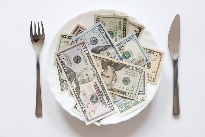 U.S. dollars on a plate with knife and fork.