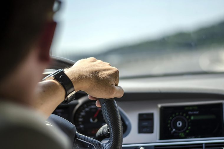 Person driving with hand on the steering wheel