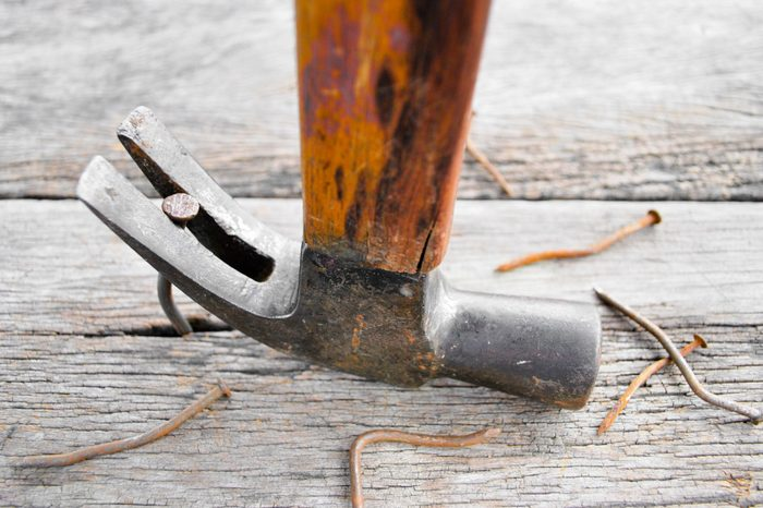 Carpenter Pulling a Nail on wood