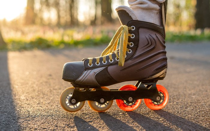 Close view of inline skates. Outdoor inline skating on smooth concrete ground. Ice skating at sunset. Background with bokeh