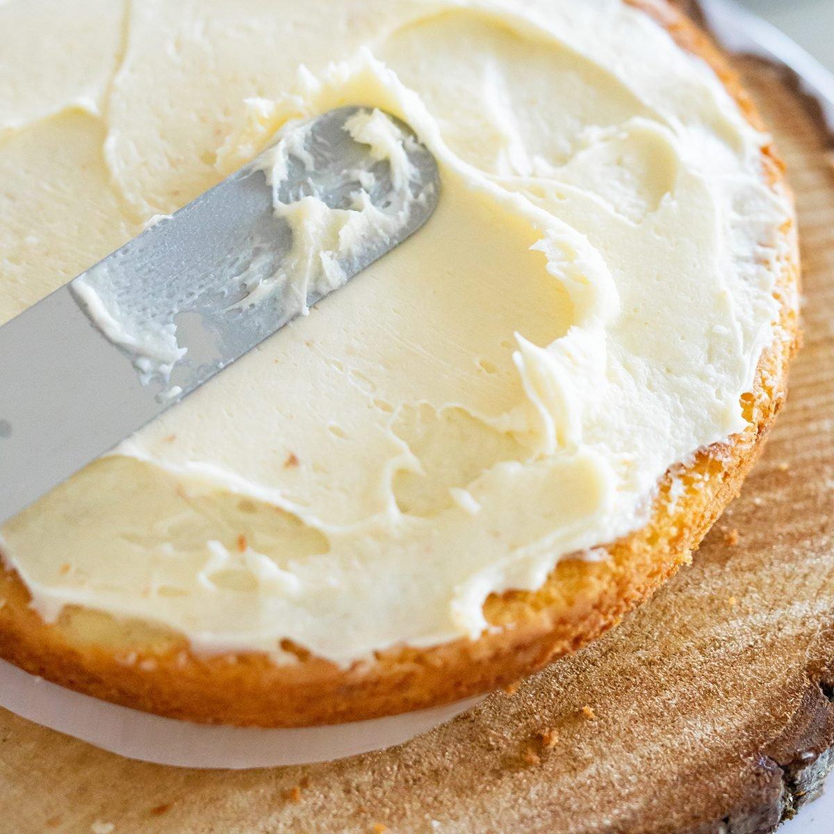 woman icing vanilla cake with metal spatula ; Shutterstock ID 1485154997; Job (TFH, TOH, RD, BNB, CWM, CM): TOH