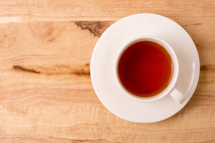Cup of tea on a wooden background top view.