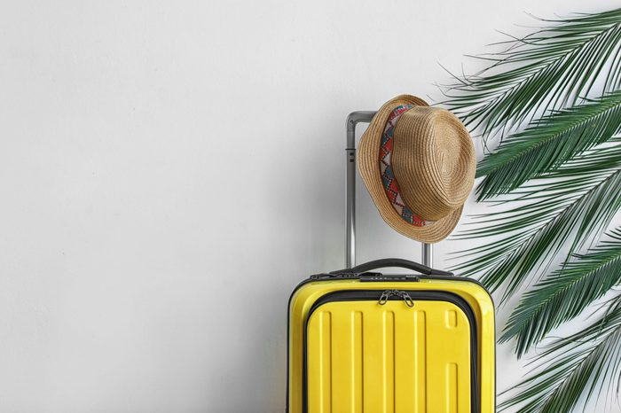 Bright yellow suitcase with hat and palm branches on light background