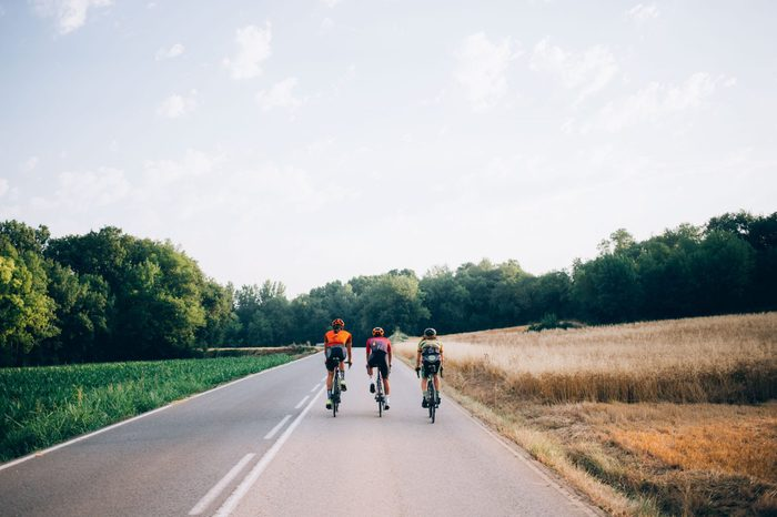Three cyclists on road bikes ride in distance on carbon bicycles during vacation in spain, healthy lifestyle, friendship and summertime