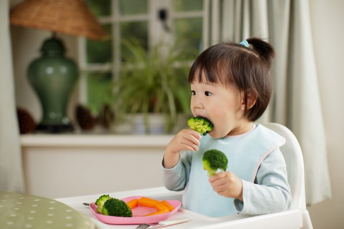 toddler girl eating healthy vegetable sitting on high chair beside a dinner table at home