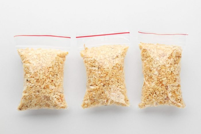 Ziploc bags with granulated dried garlic on white background