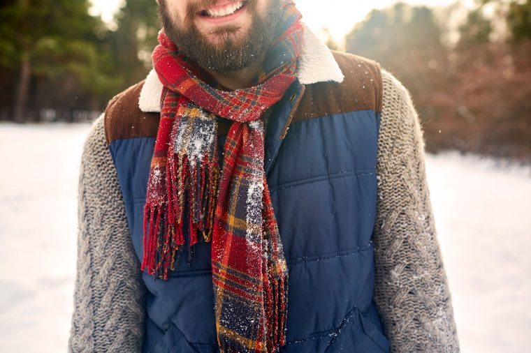 Bearded man in a scarf and winter vest in the snow