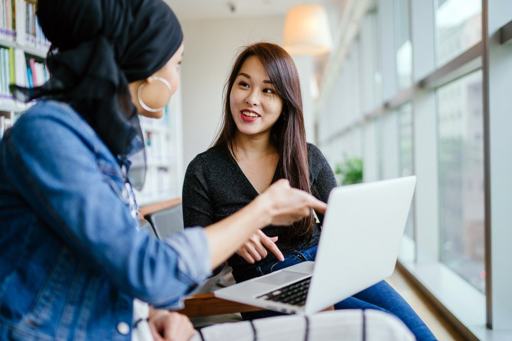 A young and attractive Chinese Asian woman has a business meeting with a Malay Muslim woman. They are both sitting in an office and talking over a laptop computer during the day.