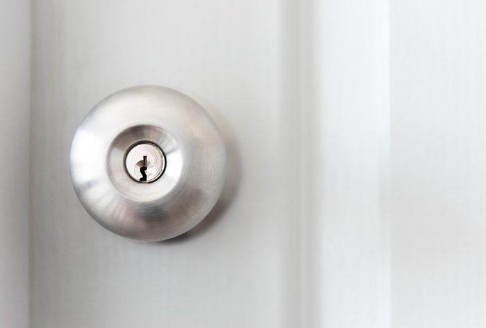 white door with metal doorknob is regular lock style in a house, copy space.