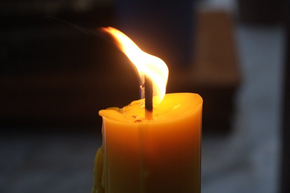 Close up burning yellow candle light against a dark blurred background