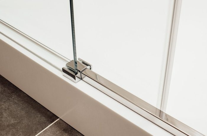 Close to lower metal fastening of the sliding glass door into the shower cabin view in the interior