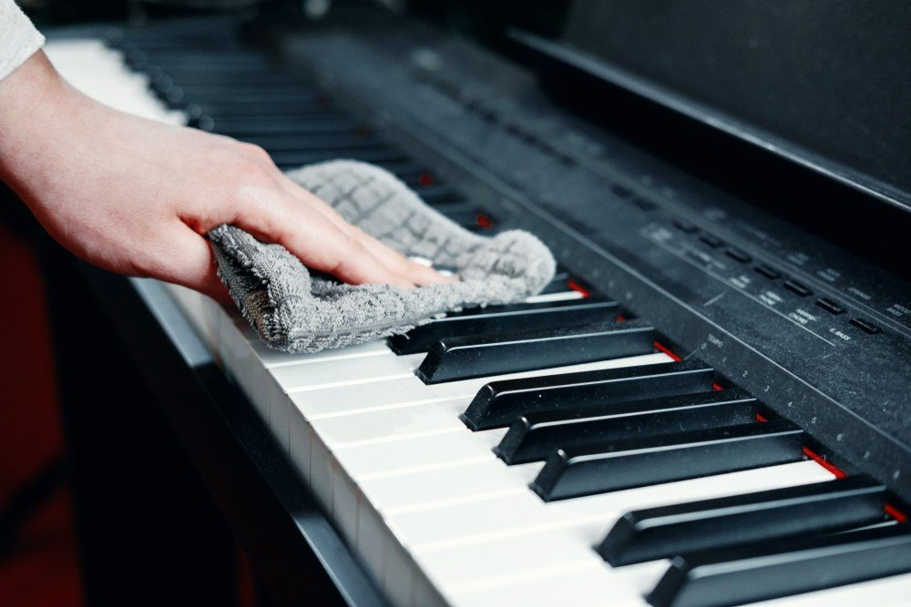 dirty piano, wipe dust from a piano, a woman's hand with a rag for cleaning