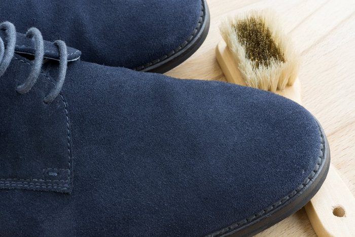 Cleaning a pair of blue suede shoes on a light wood