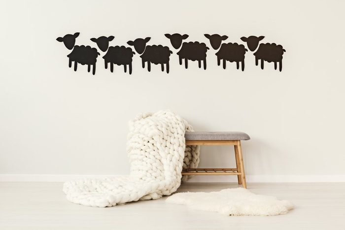 Big, handmade, woolen blanket thrown on a grey bench standing under decorative paper sheep on the wall in simple interior