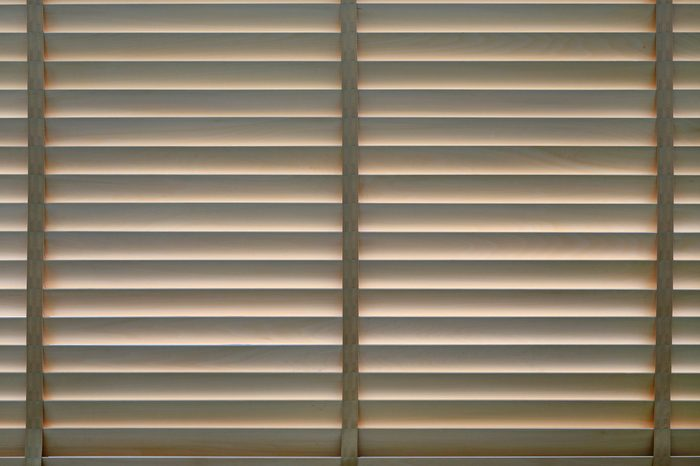 Wood blinds or curtain by the window.
