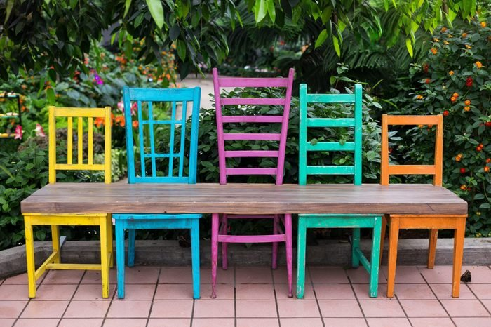 Bench made of five wood chairs in different sizes and colours and wood plank