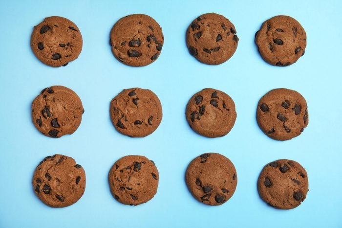 Delicious chocolate chip cookies on color background, flat lay