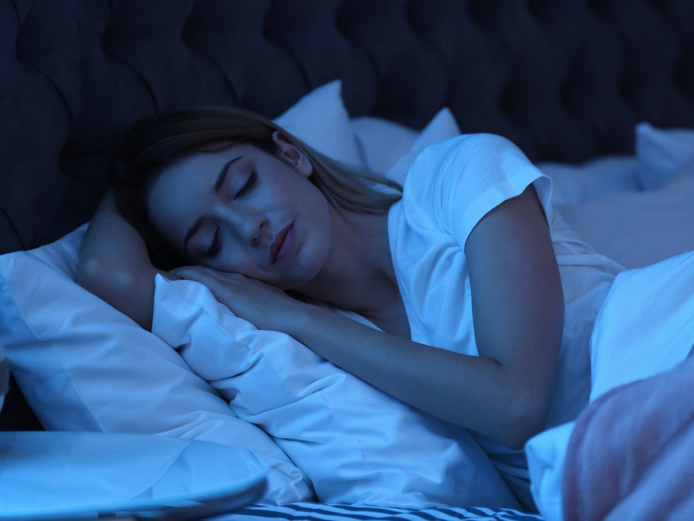 Young woman sleeping in bed at night