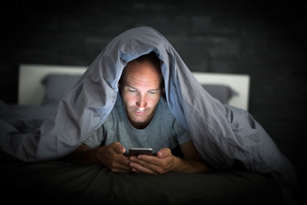 Man under covers while looking at smartphone