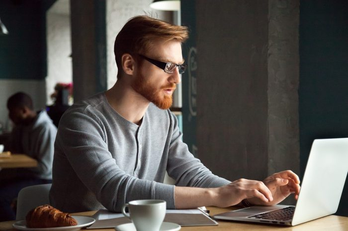 Focused millennial redhead man in glasses using laptop sitting at cafe table, serious businessman freelancer distantly working or studying on computer typing online using free wifi in coffee shop