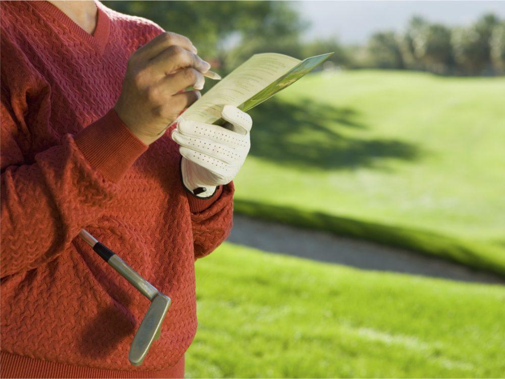 Person filling in golf scorecard