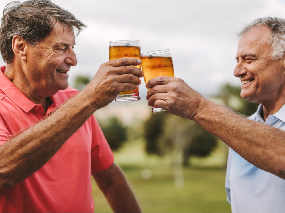Two men holding beers on golf course