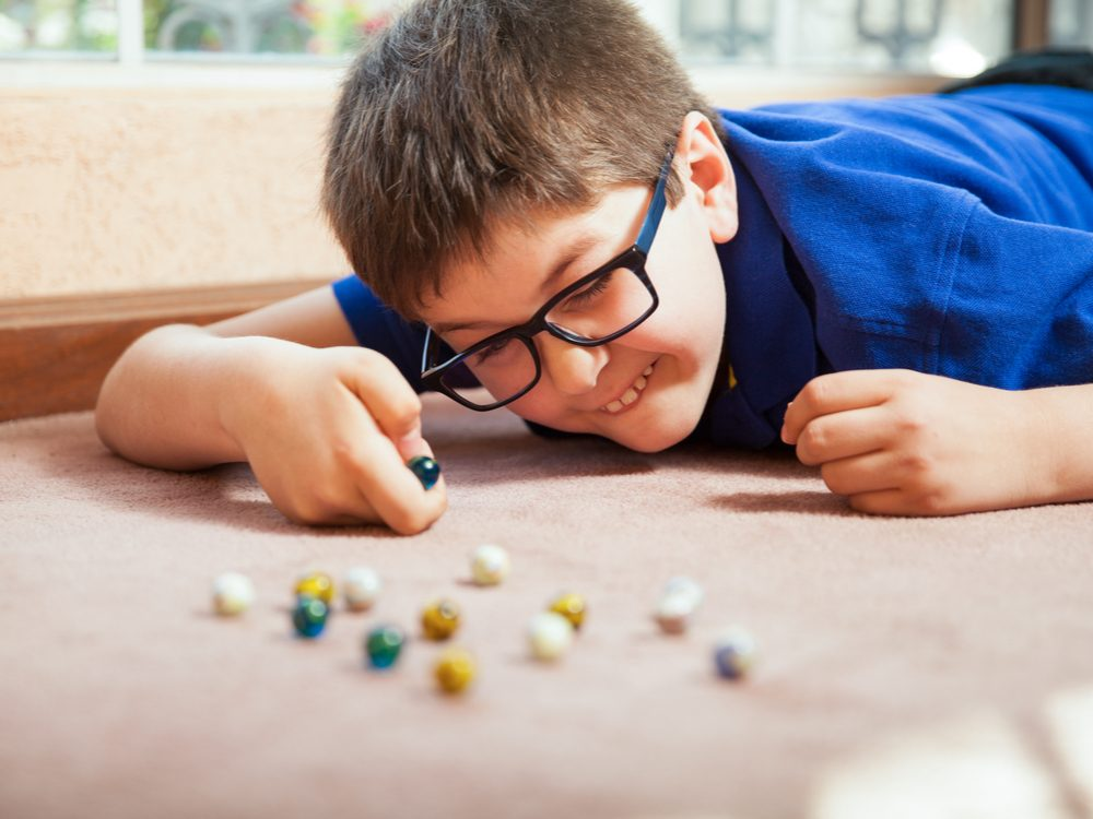 Young boy playing marbles