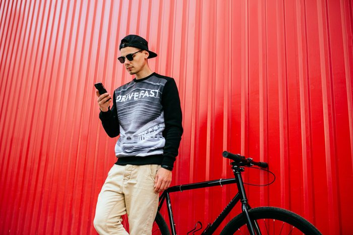 Concentrated trendy young man using a mobile phone, browsing websites, sitting on bike. Outdoors. Wearing stylish clothes, sunglasses, in cap.