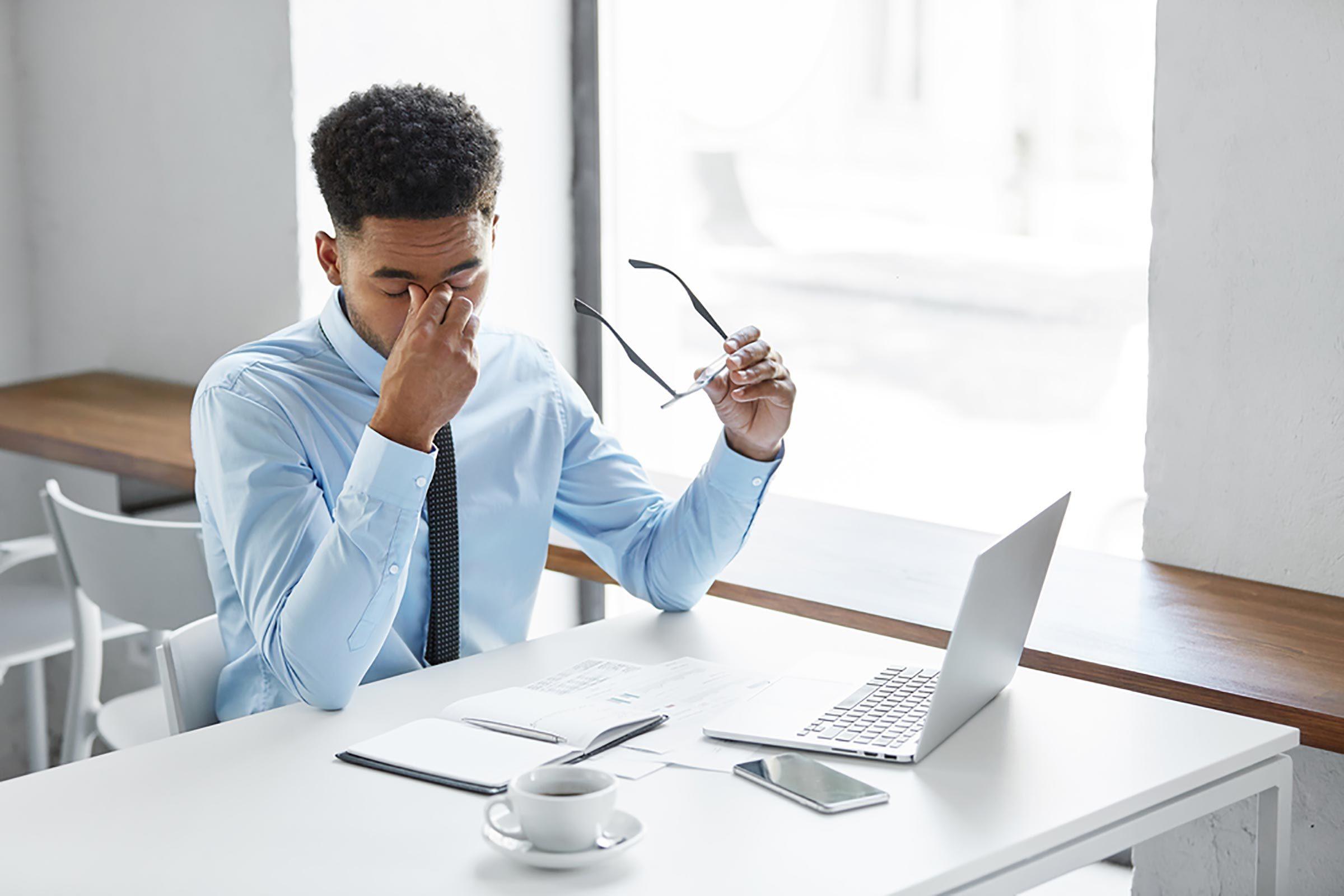 Man at his desk rubbing his eyes