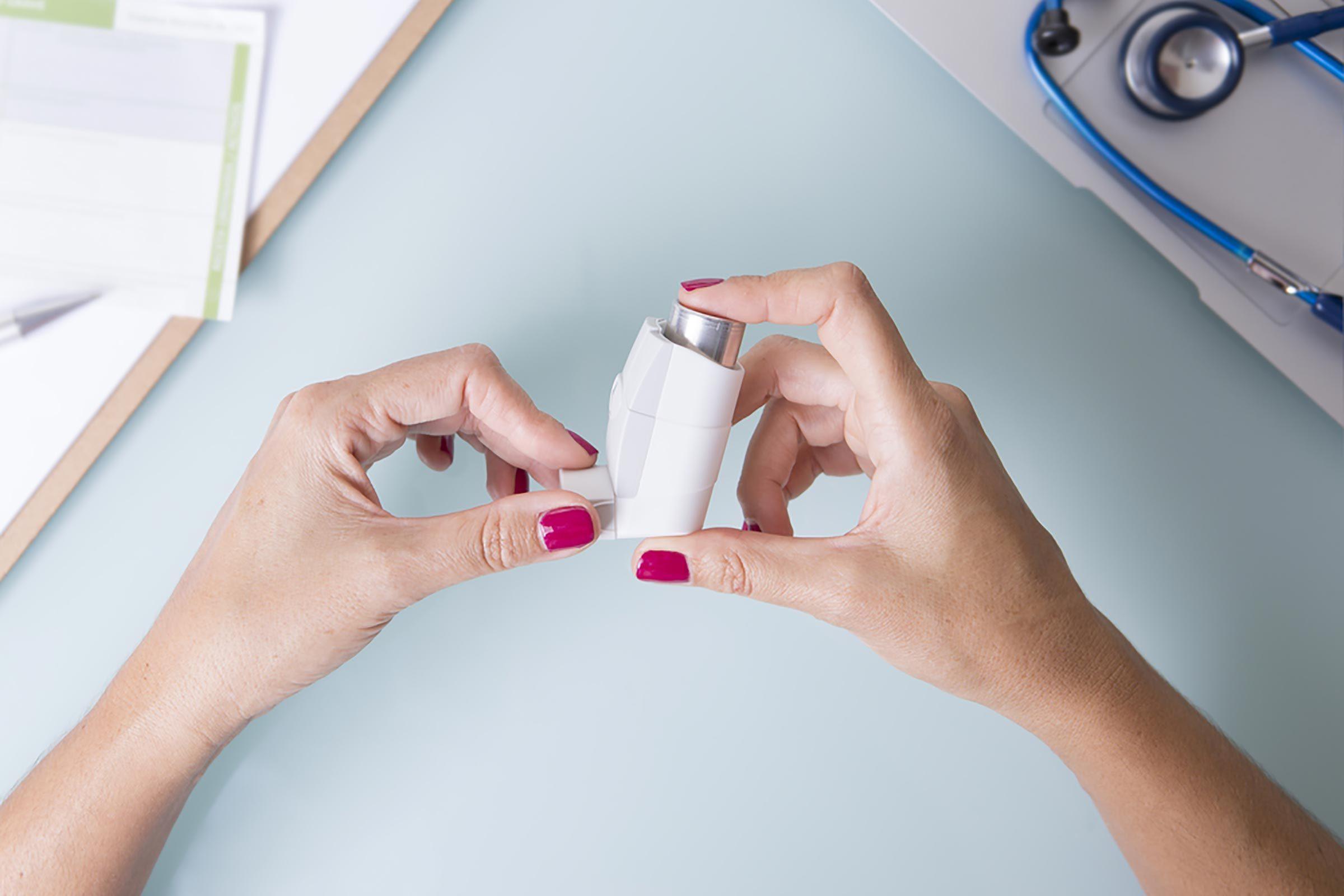 Woman holding an asthma inhaler