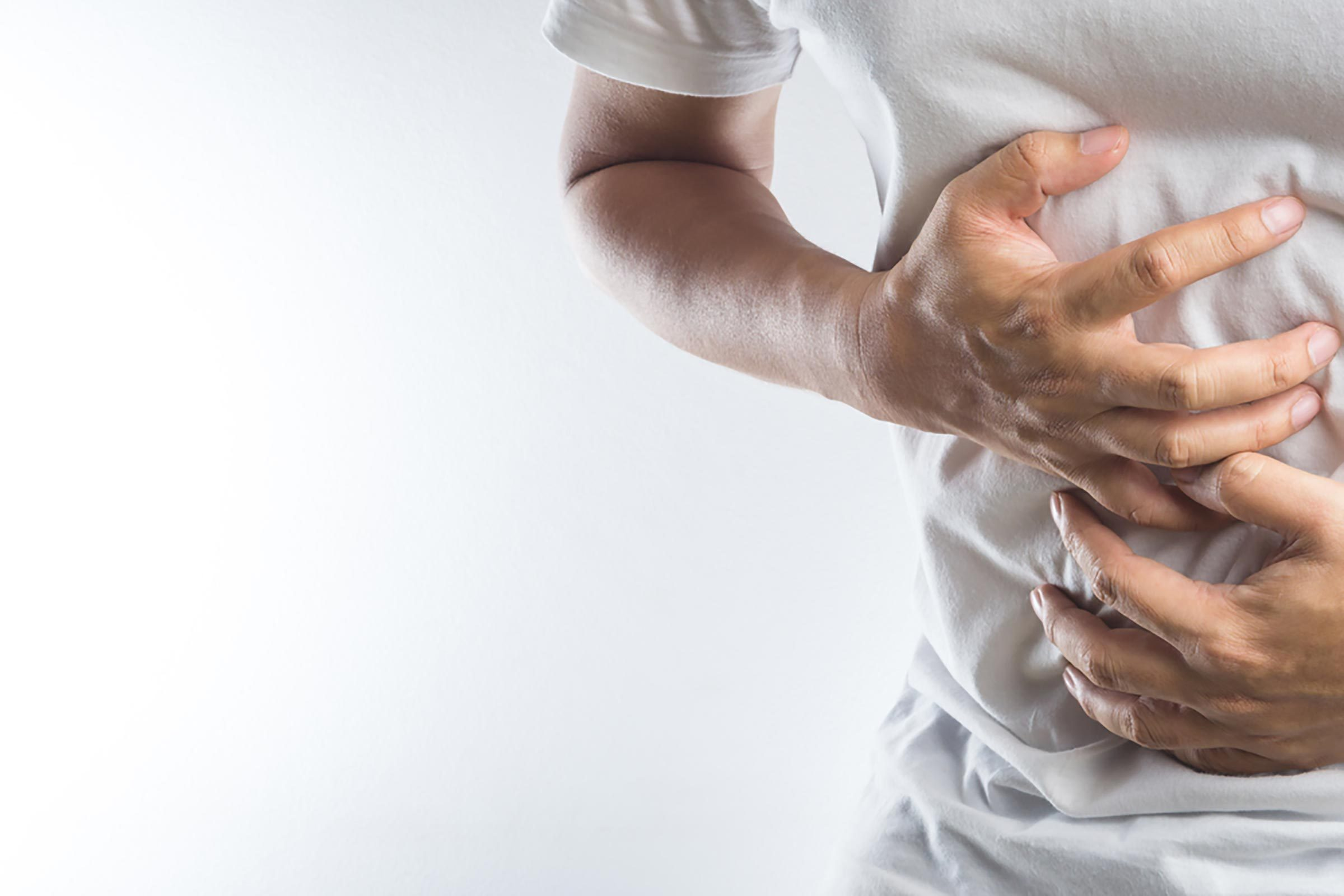 Man in a white t-shirt clutching his stomach