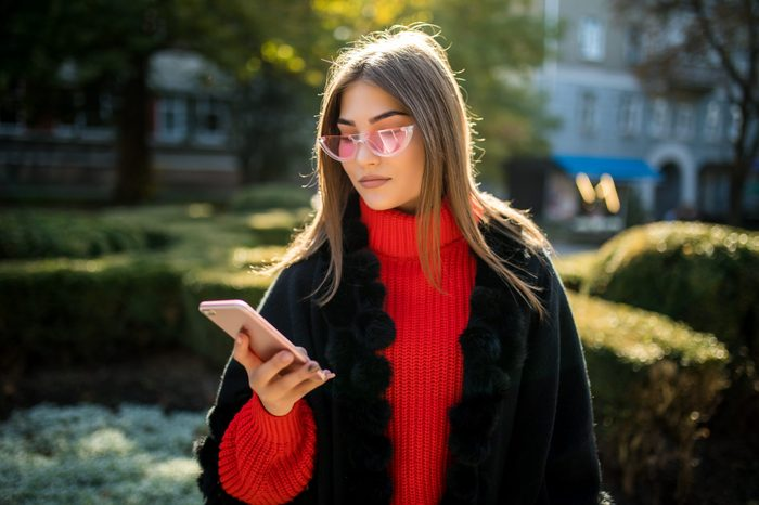 Happy woman walking and writing or reading sms messages on line on a smart phone