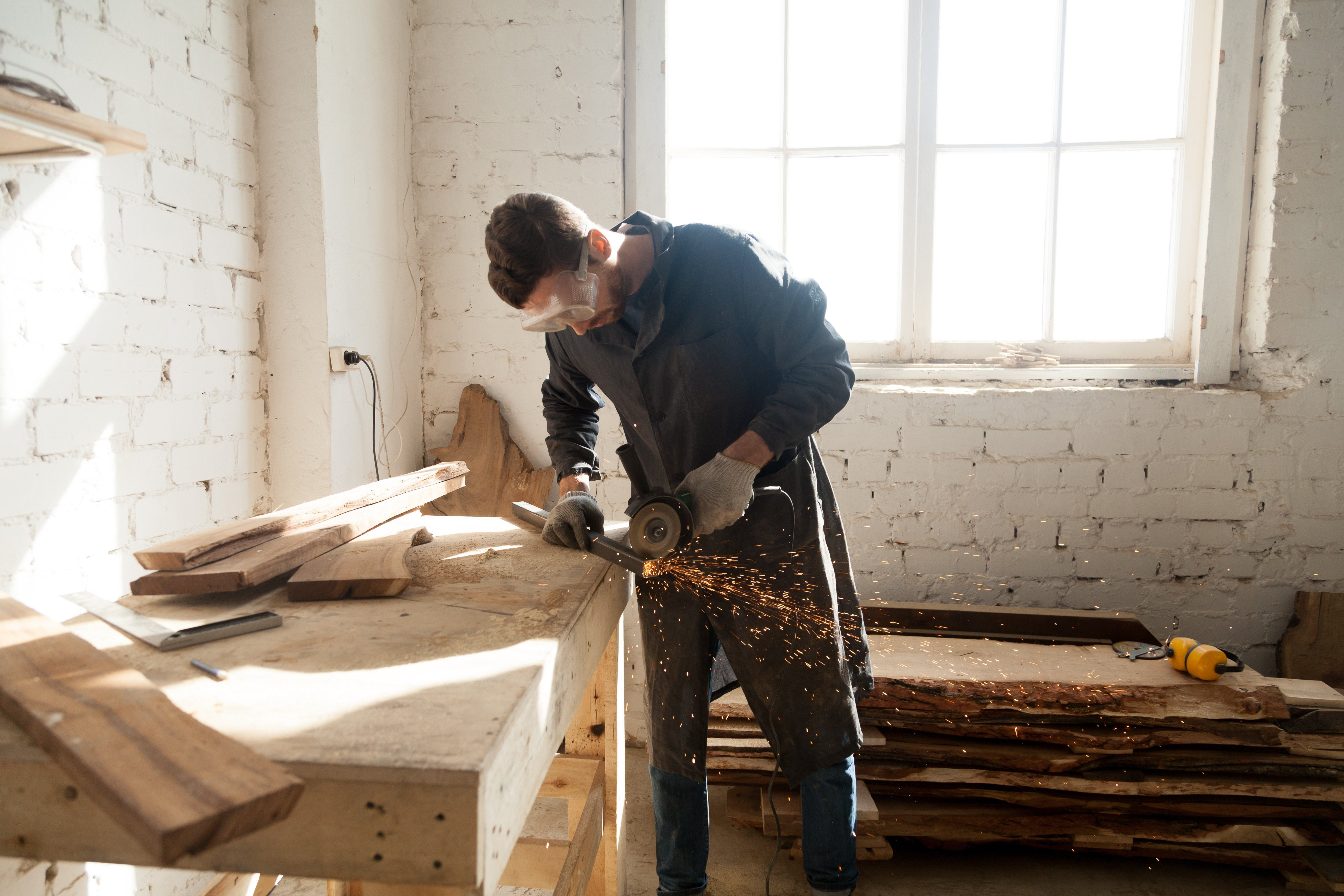 Worker cutting metal plank with angle grinder in workshop. Young man choosing skilled labor trades as first profession. Starting own small business, find side job in furniture manufacturing concept