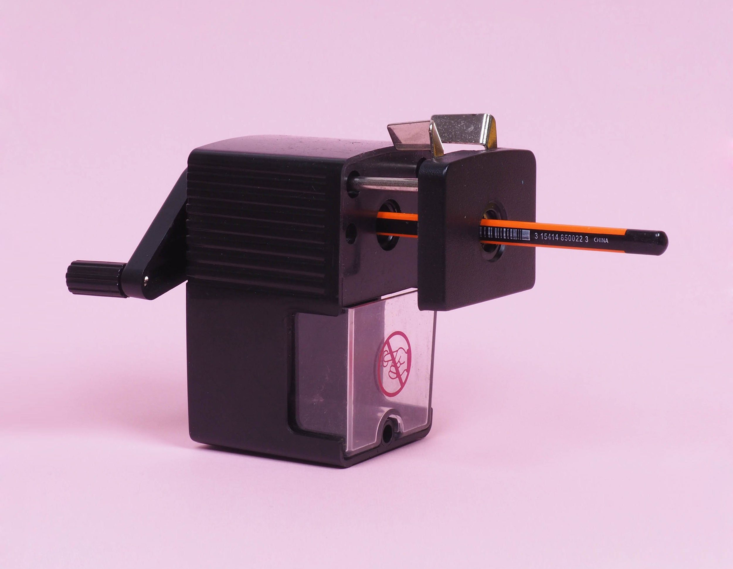 Vintage black pencil sharpener in bright pink background. Retro look pencil sharpener for school and office work.