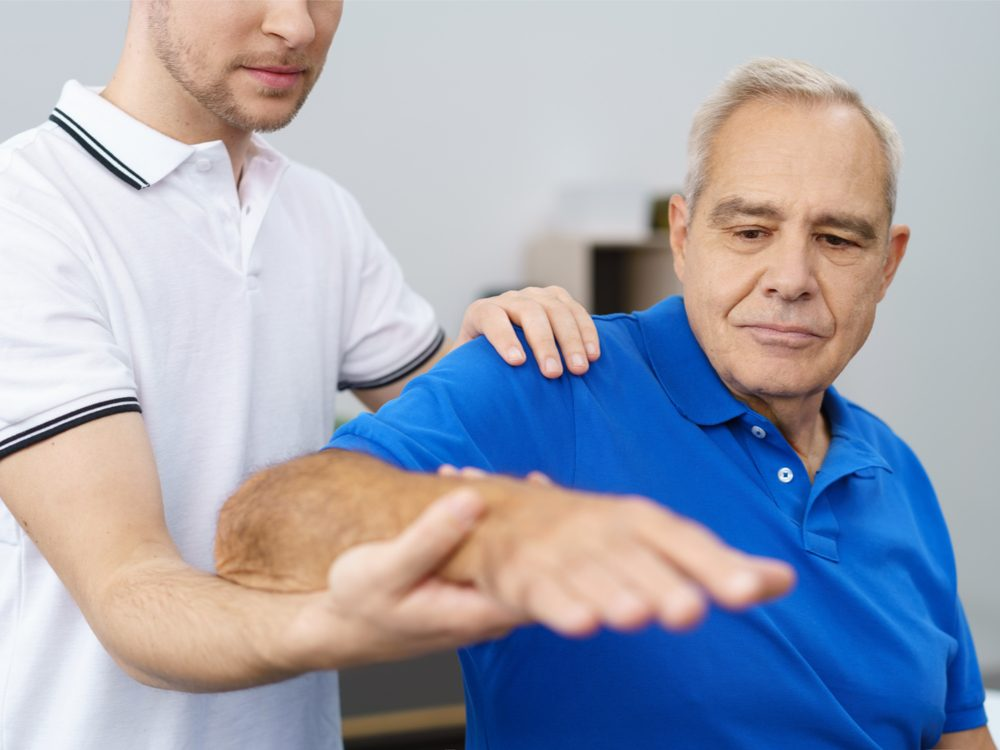Man holding out arm during physiotherapy