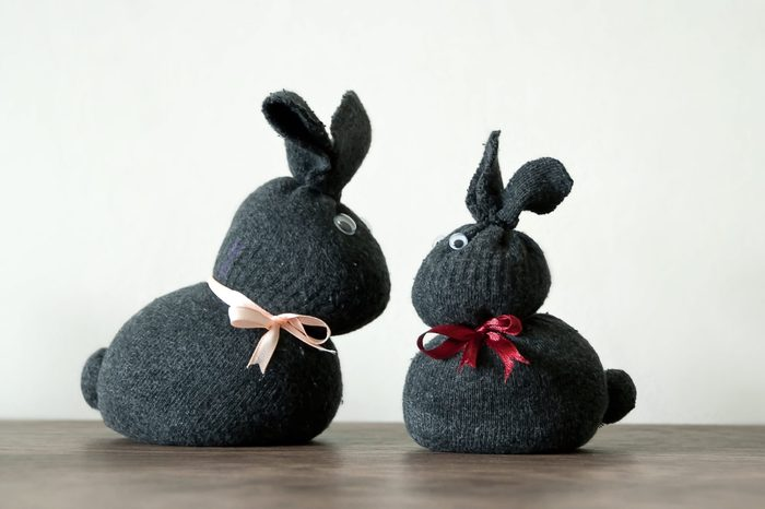 Easter decoration, two cute bunny rabbits, made of textile gray socks with ribbons and eyes. Wooden and light background. Handmade decoration, children joy and activity at home. Easter concept.