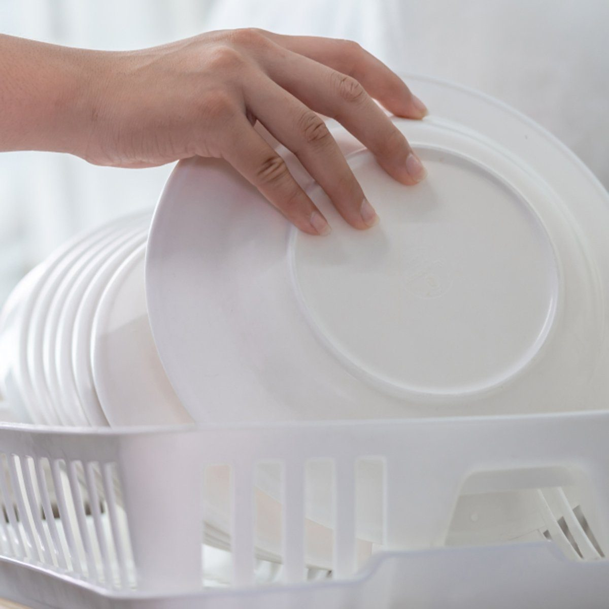 Hand of woman putting just washed clean plate in the dish rack