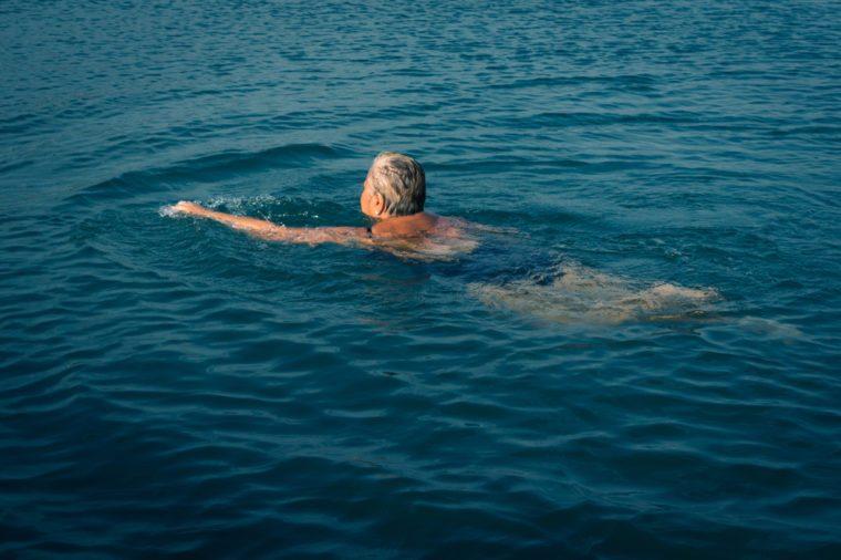 Senior man swimming in lake