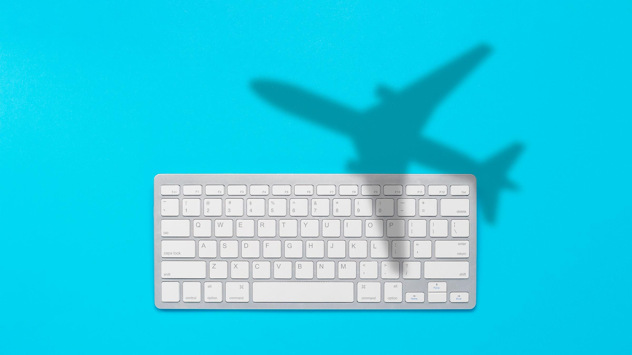 Keyboard and shadow of a flying plane on a blue background. The concept of buying tickets on the Internet online, booking tickets. Flat lay, top view.