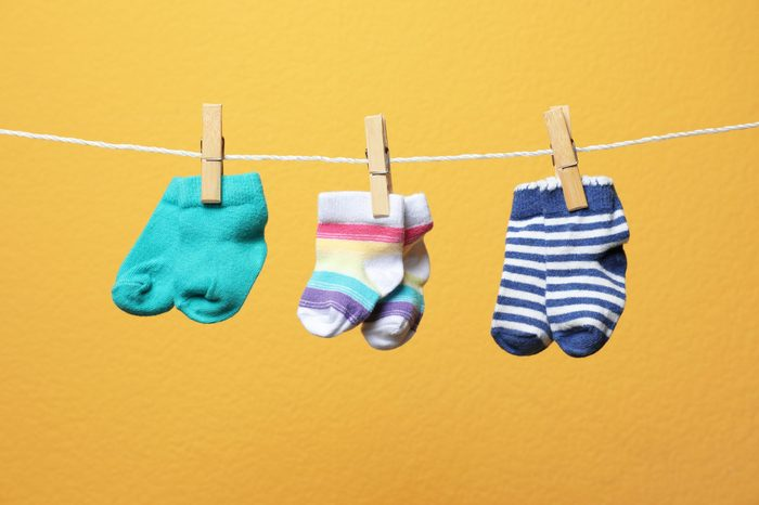 Different socks for baby on laundry line against color background