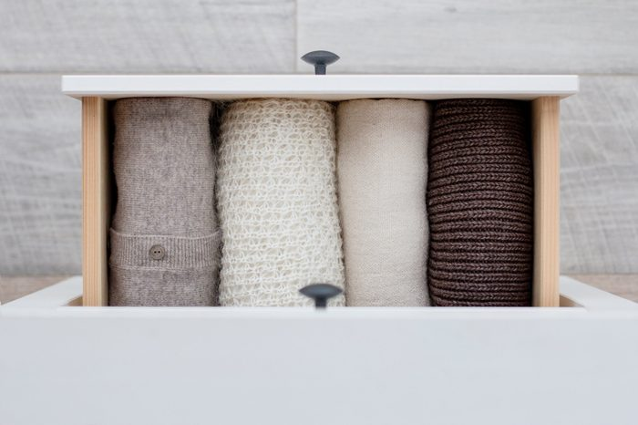 warm knitted women's clothing in brown, white and beige colors in the drawer of the chest of drawers on the background of the wooden floor, top view