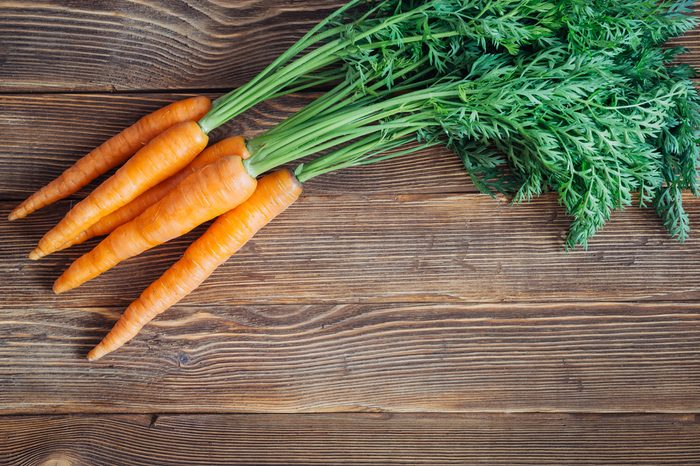 Close up of fresh carrot on rustic wooden background, top view